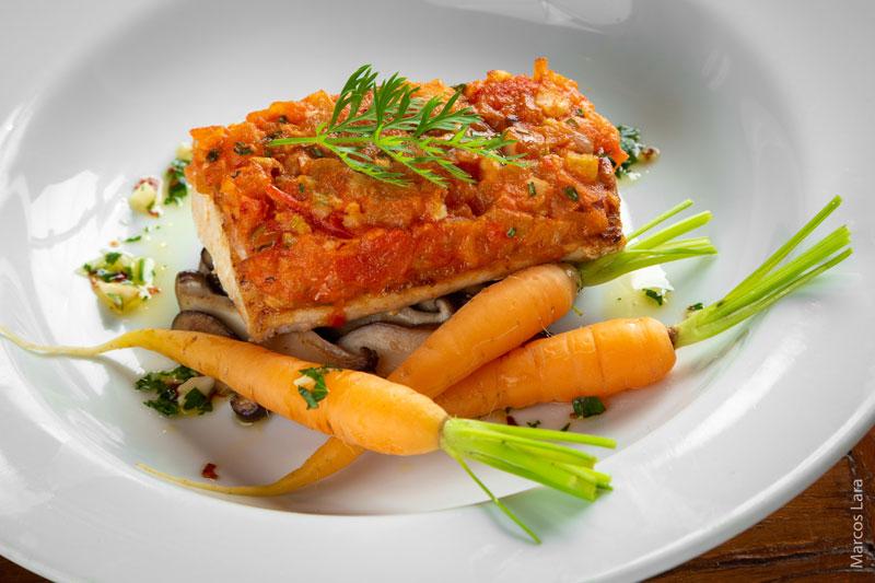 Peixe em crosta de tomate e castanha com mini cenouras e cogumelos ao molho de ervas frescas